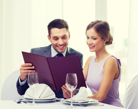 dressed: restaurant, couple and holiday concept - smiling couple with menu at restaurant Stock Photo