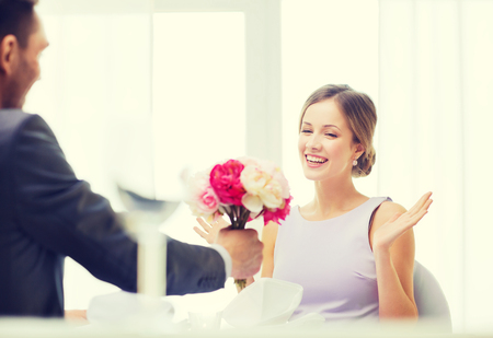 recieving: restaurant, couple and holiday concept - amazed woman recieving bouquet of flowers from husband or boyfriend at restaurant Stock Photo