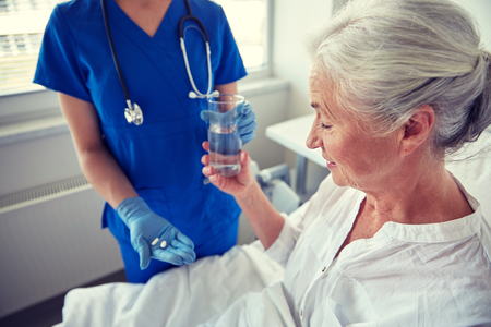 doctor giving glass: medicine, age, health care and people concept - nurse giving medication and glass of water to senior woman at hospital ward