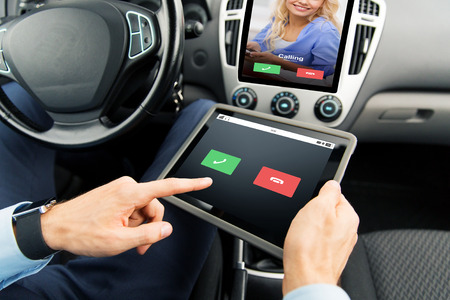 incoming: transport, business trip, technology, communication and people concept - close up of male hands holding tablet pc computer with incoming call on screen in car Stock Photo