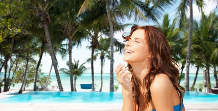 travel, tourism, summer vacation and people concept - happy beautiful woman over beach or resort hotel swimming pool background Stock Photo