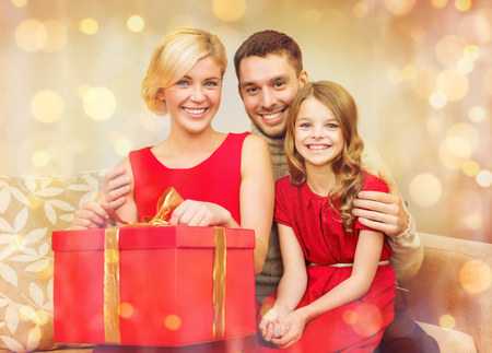 family, christmas, x-mas, winter, happiness and people concept - happy family opening Stock Photo