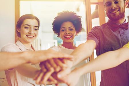 jovenes estudiantes: negocio, de inicio, el gesto, la gente y el trabajo en equipo - concepto de equipo creativo feliz con las manos en la parte superior de cada uno en la oficina
