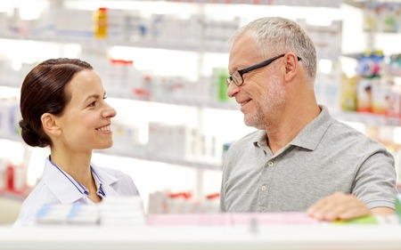 health care and medicine: medicine, pharmaceutics, health care and people concept - happy pharmacist talking to senior man customer at drugstore