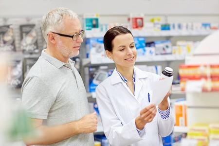 la medicina, la farmacia, la atención de la salud y la gente concepto - farmacéutico feliz y clientes hombre mayor con la droga y receta en la farmacia