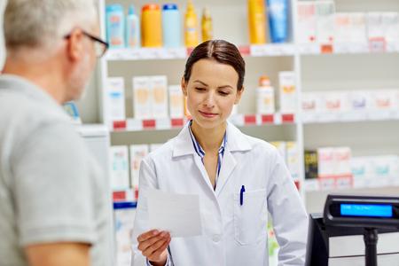 medicine, pharmaceutics, health care and people concept - pharmacist reading prescription and senior man at drugstore cash register