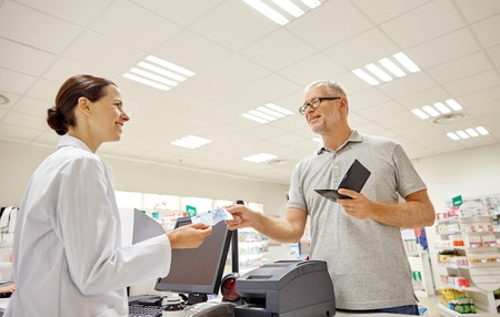 pharmaceutics: medicine, pharmaceutics, health care and people concept - smiling senior man with wallet giving money to pharmacist at drugstore cash register