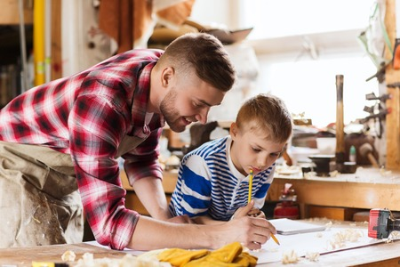 chippy: family, carpentry, woodwork and people concept - happy father and little son with blueprint at workshop Stock Photo