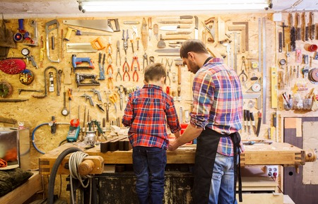 woodwork: family, carpentry, woodwork and people concept - father and little son working with wood plank at workshop