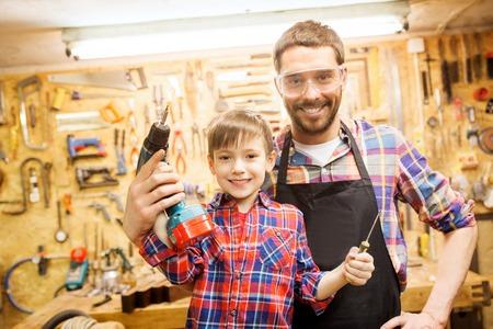 Familie, Zimmerer, Holzarbeiten und Menschen Konzept - glücklicher Vater und kleiner Sohn mit Bohrmaschine und Schraubenzieher an der Werkstatt arbeiten Standard-Bild