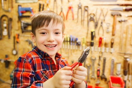 children, carpentry, profession and people concept - happy little boy with pliers at workshop