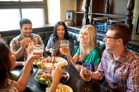 personas comiendo: leisure, eating, food and drinks, people and holidays concept - smiling friends having dinner and drinking beer at restaurant or pub