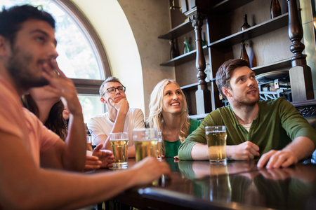 many people: people, leisure, friendship and entertainment concept - happy friends drinking beer and watching sport game or football match at bar or pub