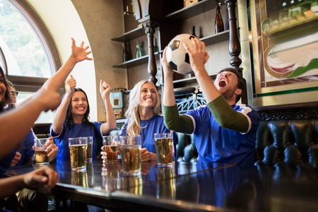 sport, people, leisure, friendship and entertainment concept - happy football fans or friends drinking beer and celebrating victory at bar or pub Stock fotó