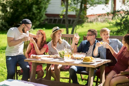 people   lifestyle: leisure, holidays, eating, people and food concept - happy friends clinking glasses and celebrating at summer garden party
