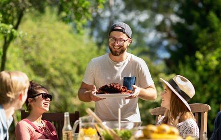 レジャー、休日、食べて、人と食のコンセプト - 夏の園遊会で夕食に肉を持つ幸せな友達