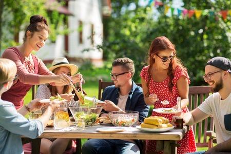 vrije tijd, vakantie, eten, mensen en eten concept - gelukkige vrienden met diner en het delen van salade in de zomer tuinfeest Stockfoto