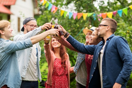 leisure, holidays, people, reunion and celebration concept - happy friends clinking glasses and celebrating at summer garden party Stock Photo