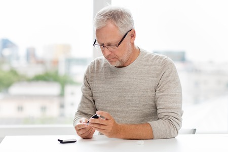 glucose: medicine, age, diabetes, health care and old people concept - senior man with glucometer checking blood sugar level at home