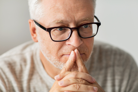 old age, problem and people concept - close up of senior man in glasses thinking Stockfoto