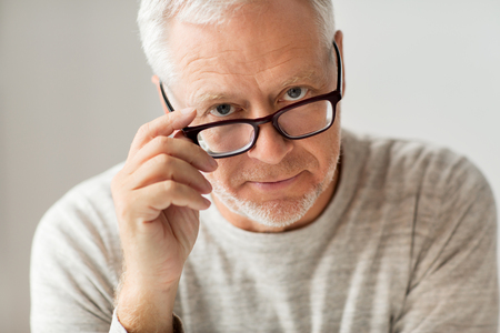 old age, problem and people concept - close up of senior man in glasses thinking Фото со стока