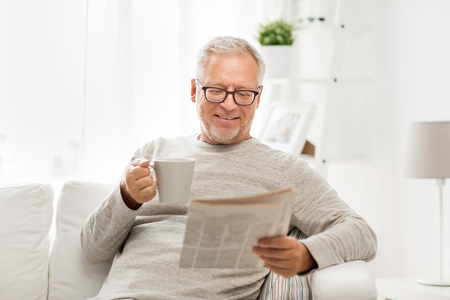 leisure, information, people and mass media concept - senior man in glasses reading newspaper at home Foto de archivo