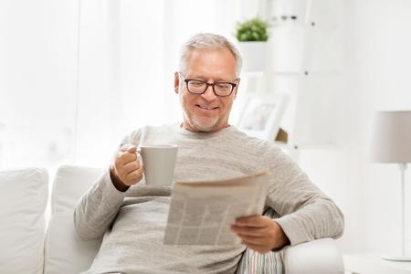 ocio, información, personas y medios de comunicación de masas concepto - hombre mayor en los vidrios que lee el periódico en su casa