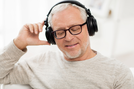technology, people and lifestyle concept - close up of happy senior man in headphones listening to music at home Stock Photo