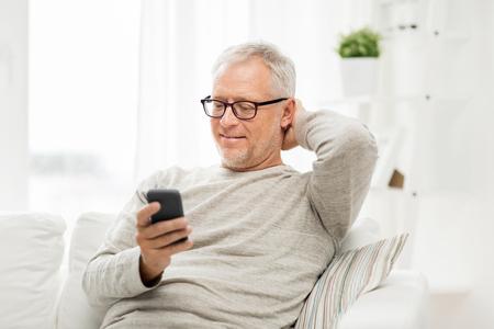 technologie, mensen, lifestyle en communicatie concept - gelukkig senior man nummerkeuze telefoonnummer en sms op smartphone thuis Stockfoto