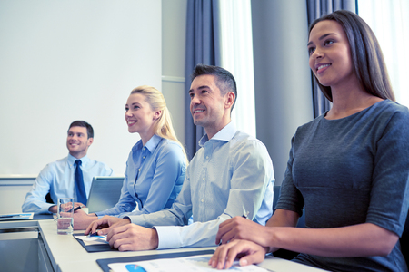 business conference: business, people and conference concept - smiling business team meeting on presentation in office Stock Photo