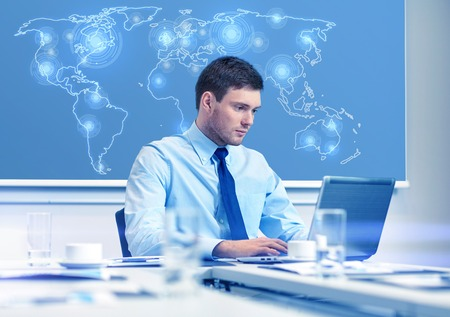 virtual world: business, people and work concept - businessman with laptop computer and virtual world map sitting in office