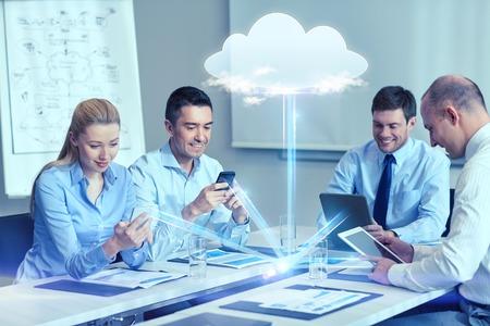 het bedrijfsleven, mensen, cloud computing en technologie concept - lachende business team met smartphones, tablet pc computers werken in het kantoor Stockfoto