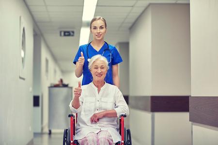 enfermera con paciente: la medicina, la edad, el apoyo, la atención de la salud y el concepto de la gente - Enfermera que toma al paciente mujer mayor en silla de ruedas y que muestra los pulgares para arriba en el pasillo del hospital