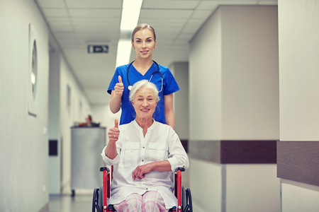 happy nurse: medicine, age, support, health care and people concept - nurse taking senior woman patient in wheelchair and showing thumbs up at hospital corridor Stock Photo