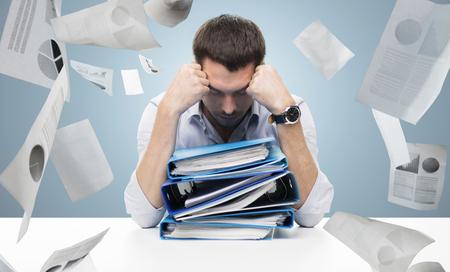 비즈니스, 사람들, 마감일, 스트레스와 서류 개념 - 파란색 배경 위에 폴더와 떨어지는 서류의 스택과 함께 슬픈 사업가