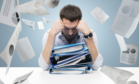 business, people, deadline, stress and paperwork concept - sad businessman with stack of folders and falling papers over blue background Reklamní fotografie