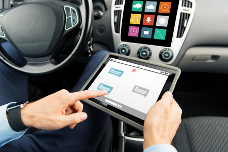Messenger: transport, business trip, technology, online communication and people concept - close up of male hands holding tablet pc computer with messenger on screen in car