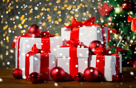 christmas, holidays, presents, new year and celebration concept - group of gift boxes and red balls under x-mas tree on wooden floor Stock Photo