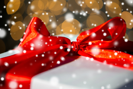 christmas, holidays, presents, new year and celebration concept - close up of gift with red bow over lights background