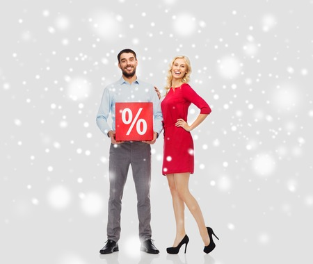 percentage sign: people, sale, christmas, winter shopping and holidays concept - happy couple with red percentage sign over snow background