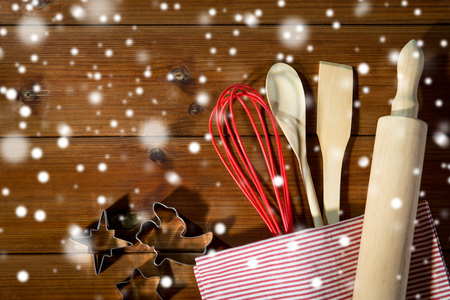 set up: baking, cooking, christmas and home kitchen concept - close up of kitchenware set for baking gingerbread on wooden board from top Stock Photo