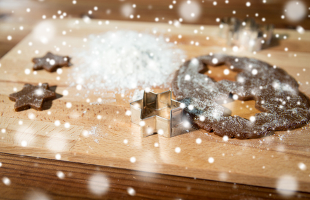 baking, cooking, christmas and food concept - close up of ginger dough, molds and flour on wooden cutting board from top Stock Photo