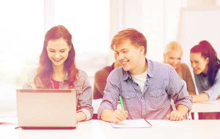 internet education: education, technology and internet concept - two smiling students with laptop and notebooks at school Stock Photo