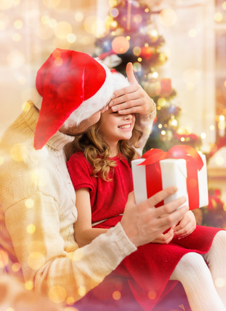 covering eyes: family, christmas, x-mas, winter, happiness and people concept - smiling father surprise daughter with gift box covering eyes with hand
