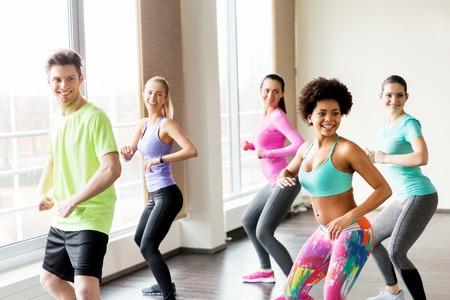 fitness, sport, dans en lifestyle concept - groep lachende mensen met coach dansen in sportschool of studio Stockfoto