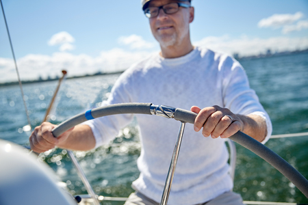 sailing, age, tourism, travel and people concept - close up of happy senior man in captain hat steering wheel and navigating sail boat or yacht floating in sea