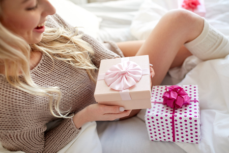prázdniny, narozeniny, ráno a lidé koncepce - zblízka šťastné mladé ženy dárkové krabičky nebo dárky v posteli v ložnici domů Reklamní fotografie