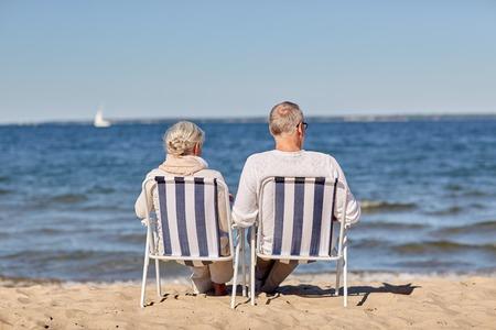 vecchiaia: Famiglia, vecchiaia, viaggio, turismo e persone concetto - felice coppia senior seduto sulle sedie a sdraio sulla spiaggia estiva Archivio Fotografico