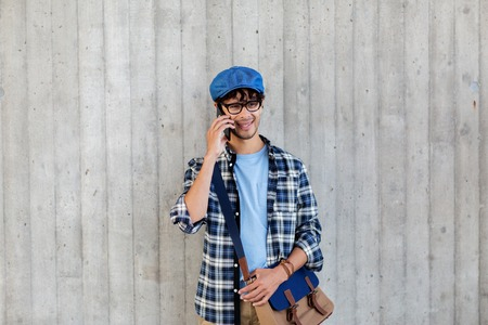 shoulder bag: leisure, technology, communication and people concept - smiling hipster man with shoulder bag calling on smartphone at street wall