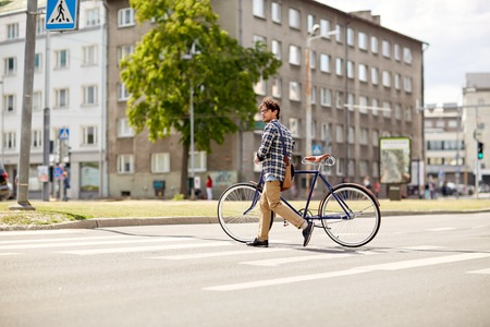 bicyclists: people, style, city life and lifestyle - young hipster man with shoulder bag and fixed gear bike crossing crosswalk on street Stock Photo